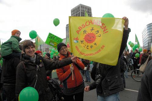写真:日本語で「原子力? おことわり」と書かれた旗を持ってデモ行進する参加者たち=ベルリン、松井健撮影