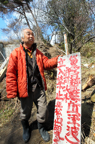 写真:手作りの避難所を造った佐藤善文さん。登り口には手書きの看板が掲げられていた=28日、宮城県東松島市、吉本美奈子撮影