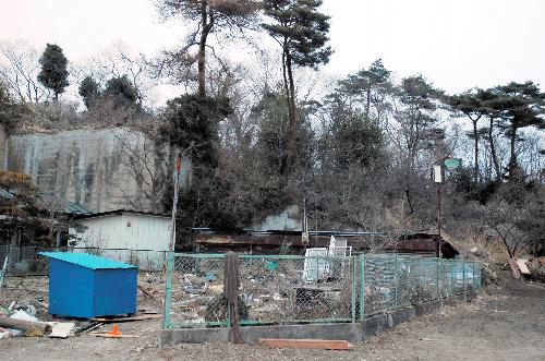 :「佐藤山」の全景。左の岩山の奥に小屋やあずま屋がある。右下が登り口。手前の家の庭にはがれきが流れ込み、家も使えなくなった=宮城県東松島市