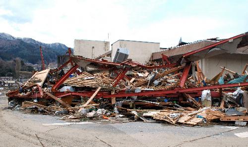 写真:津波避難用の非常通路が取り付けられていた場所(写真中央)には、流されたがれきが山積みになっていた=岩手県大船渡市三陸町越喜来、其山写す