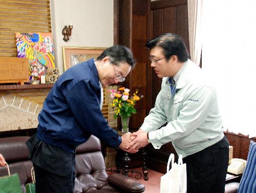 写真:懇談を終えて握手する菅家一郎・会津若松市長(右)と萩市の槌田郁利・総合政策部長=会津若松市役所