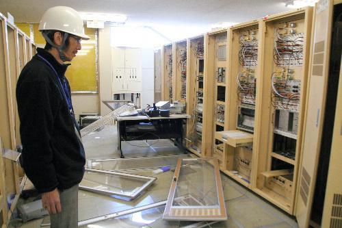 写真:壊れて配線がむき出しになった加速器の制御装置。建屋の壁が崩れて外が見えていた=茨城県つくば市の高エネルギー加速器研究機構