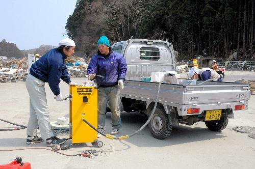 写真:手動ポンプのハンドルを回して給油する店員たち=宮城県南三陸町、岩田写す