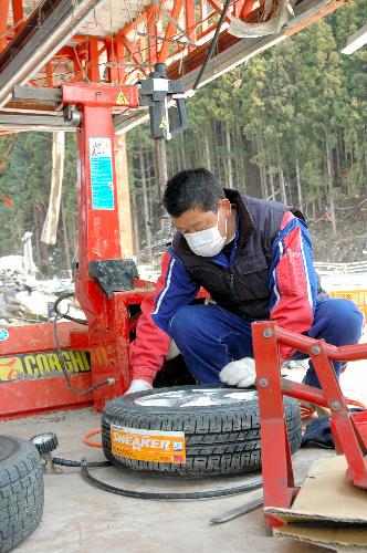 写真:手作業でタイヤ交換をする三浦文一さん=2日午後1時6分、南三陸町歌津、岩田写す