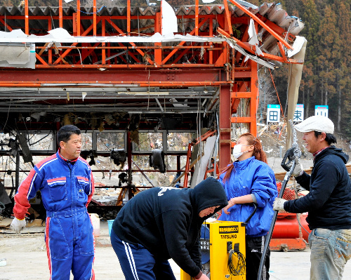 写真:3月20日、一般車両への給油を再開した三浦文一さん(左端)のガソリンスタンド=宮城県南三陸町、福岡亜純撮影