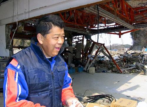 写真:全壊したスタンドで作業する三浦文一さん。津波は写真奥の伊里前湾側からやってきた。土ぼこりを舞い上げて漁船が流れてきたという=南三陸町、岩田写す