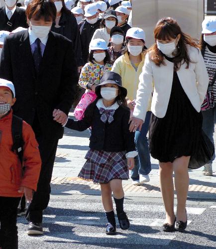 写真:放射能汚染に備え、マスクに帽子姿で入学を祝う会の会場に向かう親子連れ=6日午前9時15分、福島県いわき市平、佐々木和彦撮影