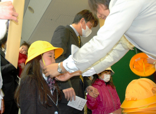 写真:「ランドセルは大丈夫でしたか」「はい」。いわき市文化センター内に設けられた永崎小学校の受付で、通学帽をかぶせてもらう新1年生=6日午前9時40分、福島県いわき市平、西堀岳路撮影