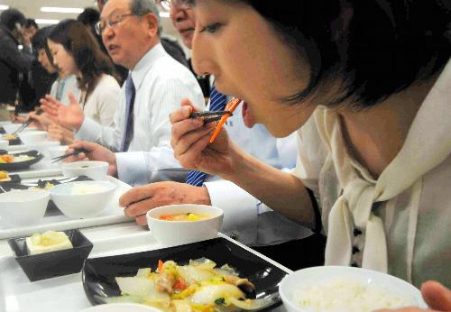 写真:被災地の野菜をつかった八宝菜を食べる社員=8日、東京都千代田区のJXホールディングス本社