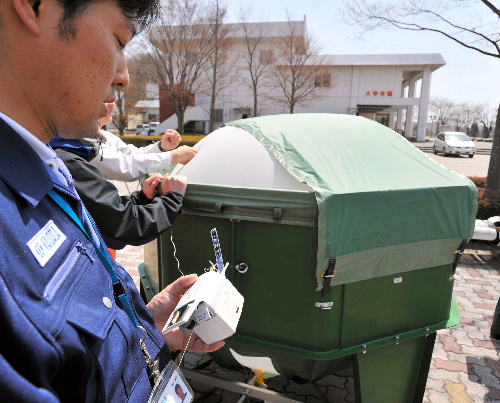 写真:空中の放射性物質を調べるラジオゾンデ(手前)を飛ばすため、小型の気球がふくらまされた=15日午前10時57分、福島市の福島大、仙波理撮影