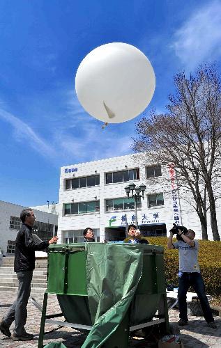 写真:空中の放射性物質を調べる装置ラジオゾンデを上空に上げるため、気球が放たれた=15日午前11時11分、福島市の福島大、仙波理撮影