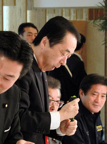 写真:農産物の風評被害を吹き飛ばそうと、JA福島から贈られたキュウリをほおばる菅直人首相(中央)=15日午後2時10分、首相官邸、飯塚悟撮影