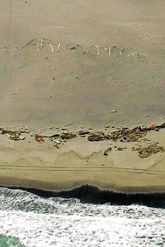 写真:仙台空港近くの浜辺に木を並べて描かれた「ARIGATO」の文字=在日米軍提供