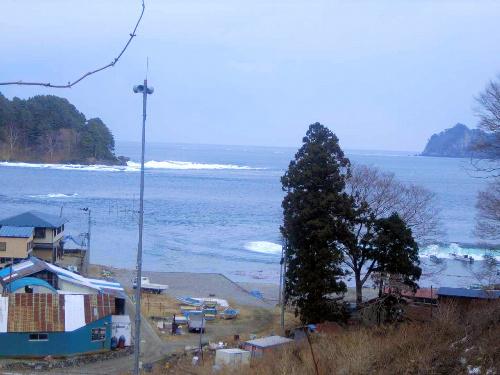 写真:いったん波が引き、2分後に向かいの岬に白波が立った=3月11日午後3時18分ごろ、岩手県宮古市川代地区、大上幹彦さん撮影、岩手県立博物館提供