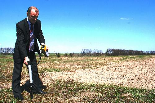 写真:菜の花による土壌改良を進めている農地で放射線量を計測するディードフ准教授=ウクライナ北部、玉川写す