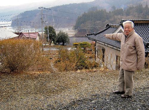 写真:白浜集落は1933年の昭和三陸大津波を機に、高所に移転。今回の津波は左奥の海から集落の下の谷を通り抜けた。熊谷さんが指さす奥の屋根が、昭和の津波で無事だった唯一の家=岩手県大船渡市