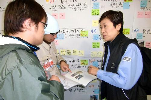 写真:被災地のボランティアセンターで担当者から説明を受ける辻元清美首相補佐官(右)=23日、岩手県大槌町、蔭西写す