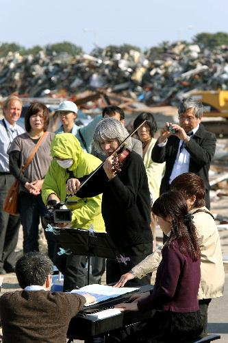 写真:野外コンサートでバイオリンを演奏する松本克巳さん(中央)ら=8日午後3時16分、宮城県名取市閖上4丁目、小宮路勝撮影