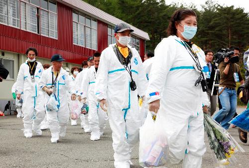 写真:「警戒区域」への一時帰宅のため、防護服を着てバスに乗り込む川内村の住民=10日午前11時2分、福島県川内村、河合博司撮影