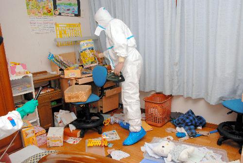 写真:防護服を着て一時帰宅し、家財道具などが散乱した部屋に入った住民=10日午後0時23分、福島県川内村、代表撮影