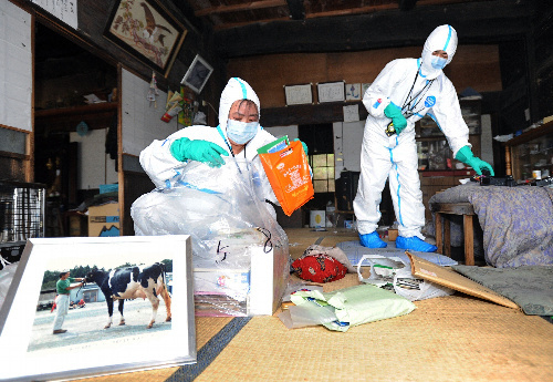写真:一時帰宅し、運び出すものをポリ袋に入れる住民=10日午後1時22分、福島県川内村、代表撮影