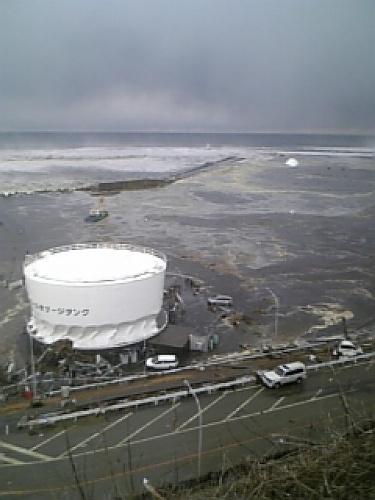写真:【写真3】津波が引いた後、タンクの根元はねじれるようにへこんでいた=3月11日、東京電力提供