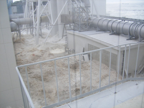 写真:【写真6】入り込んだ津波が渦を巻き、タンクが上部しか見えなくなった=3月11日午後3時43分ごろ、東京電力提供