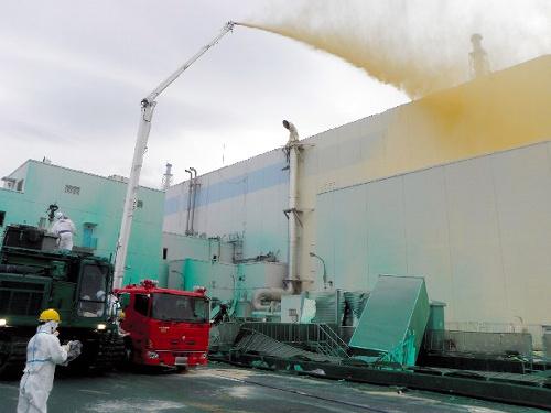 写真:福島第一原発で1号機タービン建屋の壁に散布される飛散防止剤=27日、東京電力提供