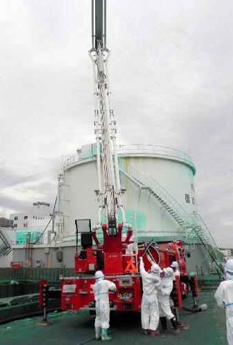 写真:福島第一原発で1号機タービン建屋に飛散防止剤を散布する東京消防庁の屈折放水塔車=27日、東京電力提供