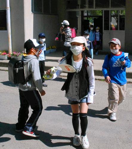 写真:放射能を浴びないように、暑くてもマスクに帽子、長袖着用の登下校。うちわであおぐ姿も見られた=24日午後、福島市渡利