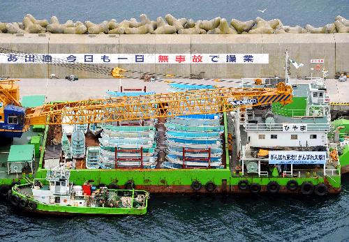 写真:岩手県の久慈港へ運搬するため、台船に積み込まれた漁船=4日午前10時49分、北海道函館市、朝日新聞社ヘリから、森井英二郎撮影
