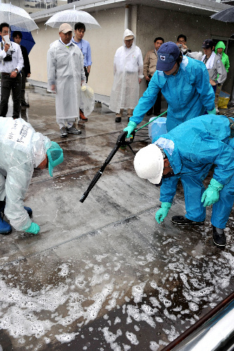 写真:福島第一小の屋上で高圧洗浄をする調査員ら=26日午前10時50分、福島市杉妻町、日吉健吾撮影