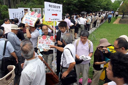 写真:脱原発を訴える人たちを前に、株主総会の会場に入るために行列する東京電力の株主たち=28日午前9時34分、東京都港区、林敏行撮影