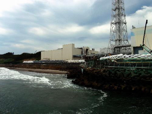 写真:福島第一原発の岸壁に造られた仮設防潮堤(右側)=6月30日撮影、東京電力提供