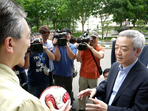 写真:「がんばれ東日本」などと書かれたサッカーボールを達増拓也・岩手県知事(左)に手渡す松本龍復興担当相=岩手県庁