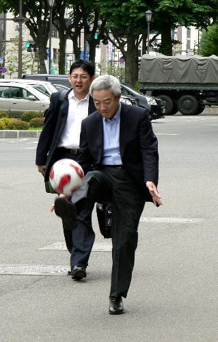 写真:「がんばれ東日本」などと書かれたサッカーボールを達増拓也・岩手県知事めがけて蹴る松本龍復興担当相。達増氏はボールを取り損ねた=3日、岩手県庁