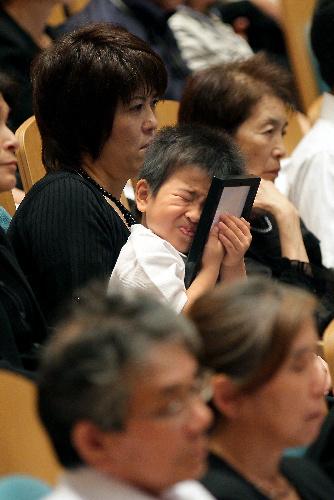 写真:福島県南相馬市の慰霊祭に出席し、津波で亡くなった父・孝行さんの遺影を抱きしめる松平征久君=3日午前、林敏行撮影