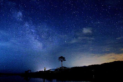 写真:一本松の上に広がった星空と天の川(左)=6日午後9時44分、岩手県陸前高田市、葛谷晋吾撮影