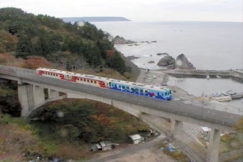 写真:震災前の海辺を走る三陸鉄道の列車=「おらほの鉄道」の一場面から、日本映画大学提供