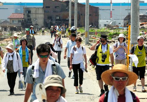 写真:がれきが残る街を歩く「復興ウオーキング」の参加者=10日、宮城県石巻市、小宮路勝撮影
