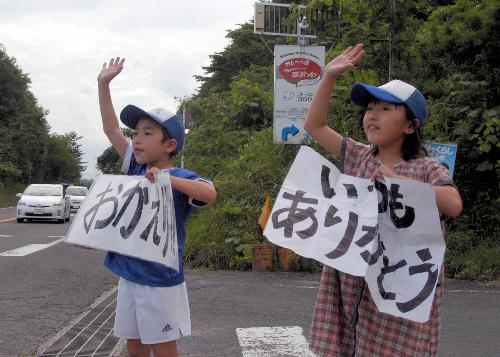 写真:警視庁の車に手を振る広野あみさんと諒君=福島市飯野町青木、山吉写す