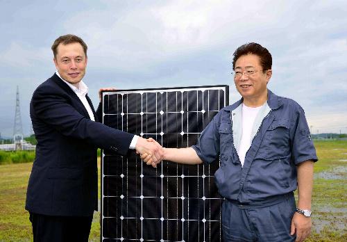 写真:寄贈するソーラーパネルを前に握手を交わすイーロン・マスク会長(左)と立谷秀清・相馬市長=29日、福島県相馬市光陽3丁目、木原写す