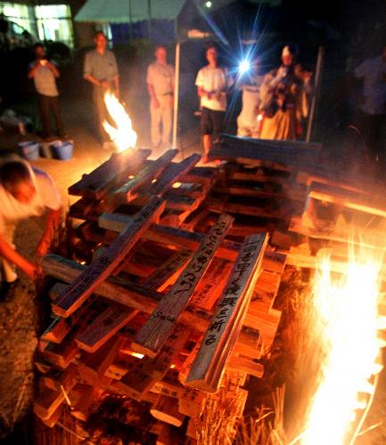 写真:メッセージが書かれた薪(まき)に火が付けられた=8日午後7時10分、岩手県陸前高田市、葛谷晋吾撮影
