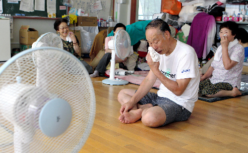 写真:厳しい暑さの中、被災者たちは扇風機の風に当たりながらも、しきりに汗をぬぐっていた=10日、宮城県石巻市の湊小学校、小宮路勝撮影