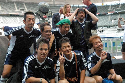 写真:ホームレス・ワールドカップの優勝杯の前で記念撮影をする野武士ジャパンの選手たち=パリ、稲田写す