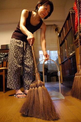 写真:掃除機をやめ、ほうきで掃除する志村瑞枝さん=東京都中野区