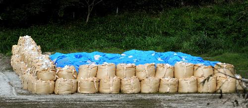 写真:放射性物質を含んだ土砂などが置かれた仮置き場。青いシートで覆われ、周囲は土嚢(どのう)で囲まれていた=14日午後、福島市大波、小川智撮影