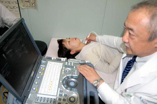 写真:8日に公開された検査のリハーサルで、医師は大学職員の首に甲状腺の超音波検査装置をあてた=福島市光が丘の福島県立医科大