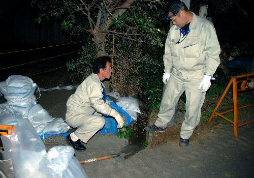 写真:高放射線量が測定された現場で土を採取する柏市の職員=21日夜、千葉県柏市根戸