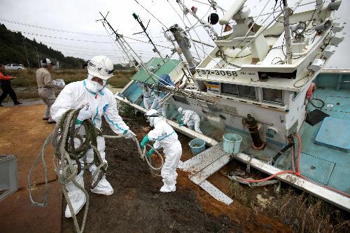 写真:陸に打ち上げられた漁船を除染するため、漁具などを運び出すボランティアたち=24日午前、福島県南相馬市鹿島区、橋本弦撮影